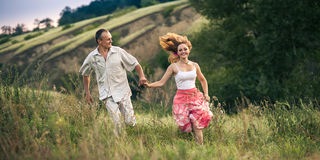 Cheerful couple in love running, Holding each other  hands on th Royalty Free Stock Photography
