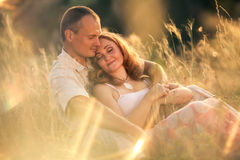 Cheerful couple in love sitting on the slope of ravine and embra. Cing Royalty Free Stock Images