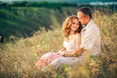 Cheerful couple in love sitting on the slope of ravine and embra. Cing Royalty Free Stock Photo