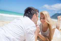 Cheerful couple lying on the beach on a sunny day Royalty Free Stock Photography