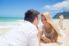 Cheerful couple lying on the beach on a sunny day Stock Images