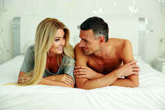 Cheerful couple lying on bed Stock Photo