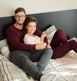 Cheerful couple lying on a bed at home Royalty Free Stock Photo