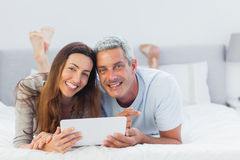 Cheerful couple lying on bed using their tablet pc Royalty Free Stock Photography