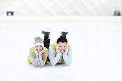 Cheerful couple lying on the skating rink stock photography