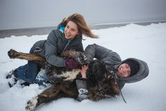 Cheerful couple lying on snow with dog. Winter Holidays, love moments, happy time.  Royalty Free Stock Image