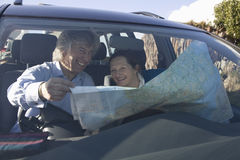Cheerful Couple With Map In Car Royalty Free Stock Photo