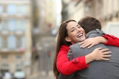 Cheerful couple meeting and hugging in the street. With copy space at side stock photo