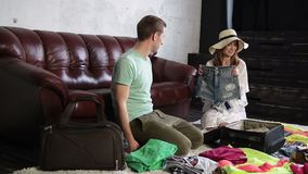 Cheerful couple packing travel bag at home stock video