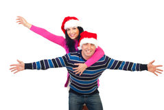 Cheerful couple in piggy back ride. Cheerful couple wearing Santa hats and  the man giving  a piggy back ride to woman and both standing with hands open and Royalty Free Stock Images