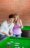 Cheerful couple playing cards on a billiard Royalty Free Stock Photo