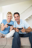 Cheerful couple playing video games in living room Royalty Free Stock Image