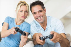 Cheerful couple playing video games in living room Stock Images