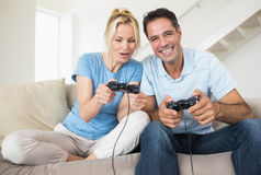 Cheerful couple playing video games in living room Royalty Free Stock Images