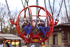 Cheerful couple preparing for the flight to attraction. Catapult in the amusement park and entertainment Stock Images