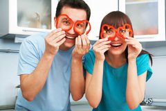 Cheerful couple preparing food in the kitchen Stock Photos