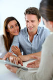 Cheerful couple ready to buy a house. Young couple meeting financial adviser Royalty Free Stock Photo