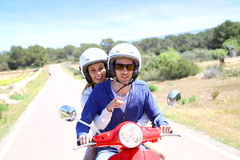 Cheerful couple on red moto visiting island. Cheerful couple riding red moto on island royalty free stock image