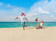 Cheerful couple in red Santa hats walking at tropical ocean sand Royalty Free Stock Photos