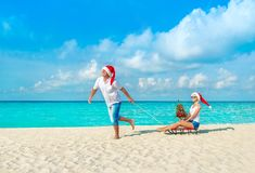 Cheerful couple in red Santa hats walking at tropical ocean sandy beach with sleds, decorated fir-tree and gift boxes. Happy New Y stock image