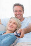 Cheerful couple relaxing at home watching tv Royalty Free Stock Image