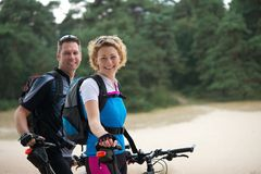 Cheerful couple relaxing outdoors with bikes Stock Image