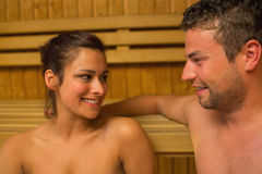 Cheerful couple relaxing in a sauna and chatting Stock Photos