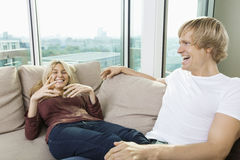 Cheerful couple relaxing on sofa at home Royalty Free Stock Images
