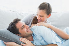 Cheerful couple relaxing on their sofa smiling at each other Royalty Free Stock Photo