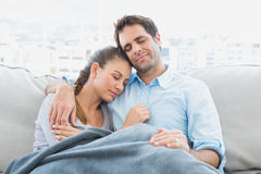 Cheerful couple relaxing on their sofa under blanket Royalty Free Stock Photos