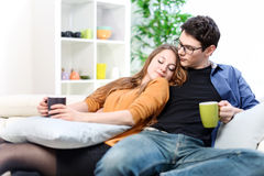 Cheerful couple relaxing together on sofa in living room Stock Images