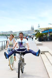 Cheerful couple riding bicycles in town Stock Photos