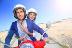 Cheerful couple riding moto in desertic island Stock Photography