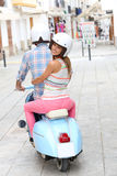 Cheerful couple riding moto in the streets. Cheerful couple riding blue moto royalty free stock images