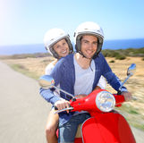 Cheerful couple riding scooter by the seaside Royalty Free Stock Image