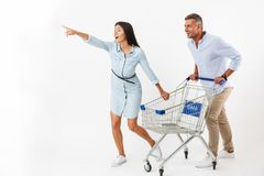 Cheerful couple running with a shopping cart. At the supermarket and pointing away isolated Royalty Free Stock Photos