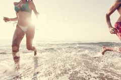 Cheerful couple running at the shore royalty free stock images