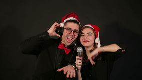 Cheerful couple in Santa hats on black background. stock video