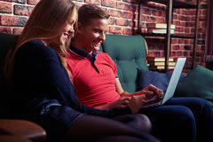 Cheerful couple searching something interesting on laptop at hom. Mid shot of lovely couple, sitting on the sofa, searching interesting information on laptop Royalty Free Stock Photo