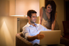 Cheerful couple searching together data on laptop Royalty Free Stock Image