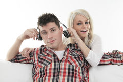 Cheerful couple sharing music in sofa at home Royalty Free Stock Images