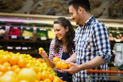 Cheerful couple shopping for organic fruit royalty free stock photo