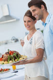 Cheerful couple showing roast chicken in the kitchen Royalty Free Stock Photos