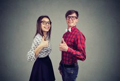Cheerful couple showing thumbs up. Side view of young content men and women showing thumbs up being in great relationship smiling at camera Stock Photos
