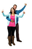Cheerful couple showing thumbs up. While standing against white background Royalty Free Stock Photo