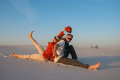 Cheerful couple sitting, back to back, in the desert. Against a blue sky on a sunny evening, laughing and having fun. Happy people get new impressions and enjoy Royalty Free Stock Photo