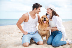 Cheerful couple sitting on the beach with dog. Cheerful young couple sitting on the beach with their dog Stock Photo