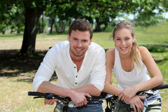 Cheerful couple sitting on bikes outdoors Stock Image