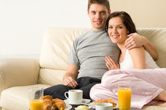 Cheerful couple sitting on couch before breakfast Royalty Free Stock Image