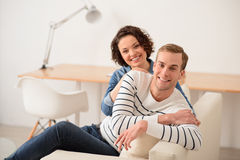 Cheerful couple sitting on the couch. Enjoy every moment. Cheerful delighted loving smiling couple sitting on the couch and expressing gladness while bonding to stock photo